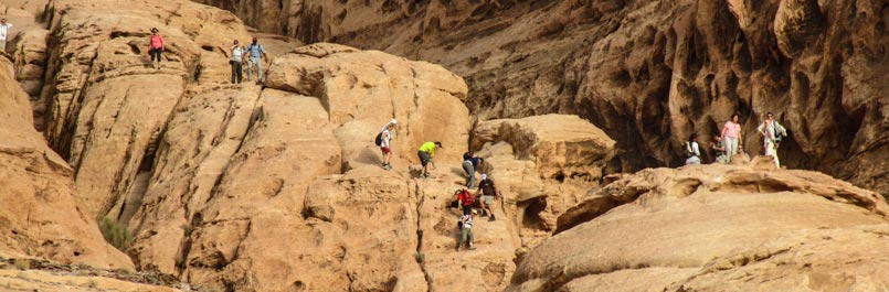 Group climbing on of the Bedouin roads to Burdah rock bridge in Wadi Rum desert