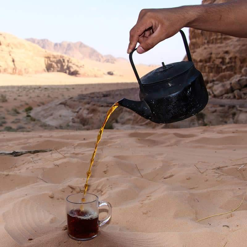 Pouring a glass of famous traditional sweet Bedouin tea