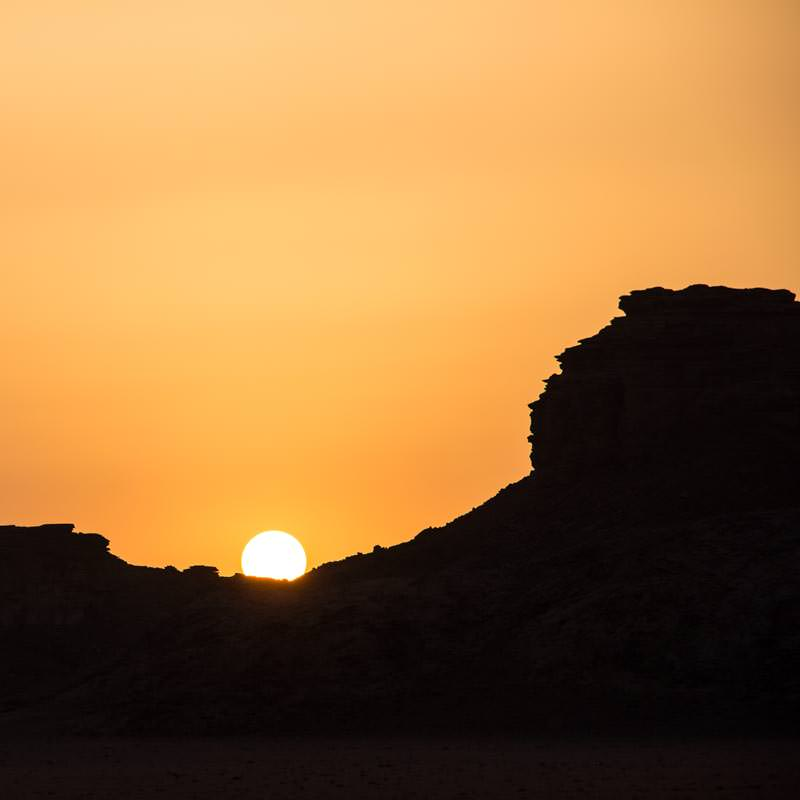 The sun setting over the mountains in Wadi Rum desert