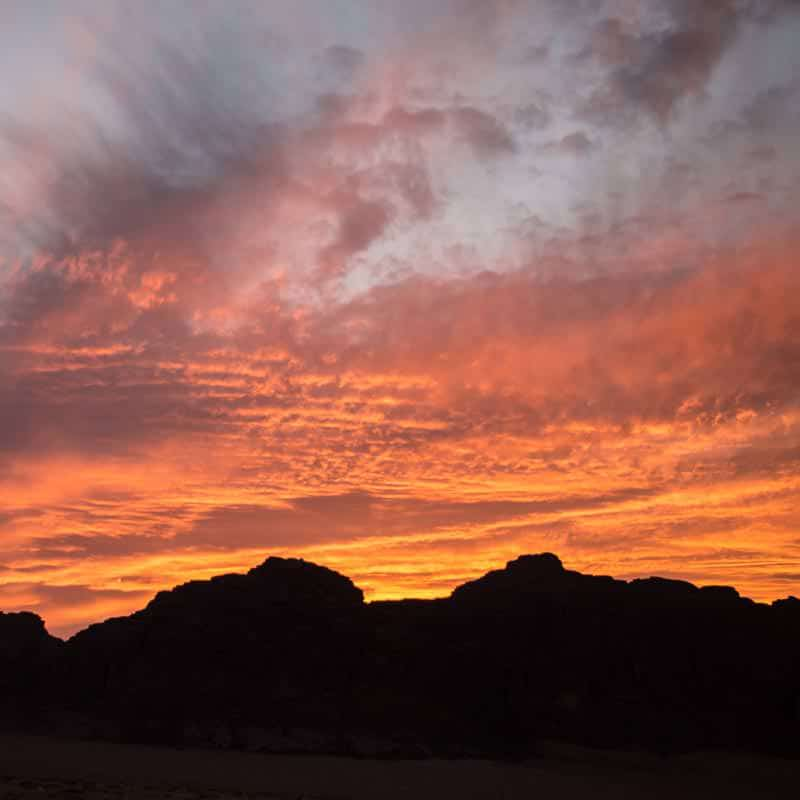 Beautifully red to gold coloured clouds at sunset in Wadi Rum desert