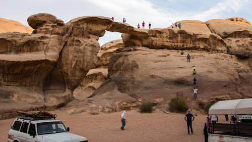 Tourists climbing Um Fruth rock bridge in Wadi Rum desert