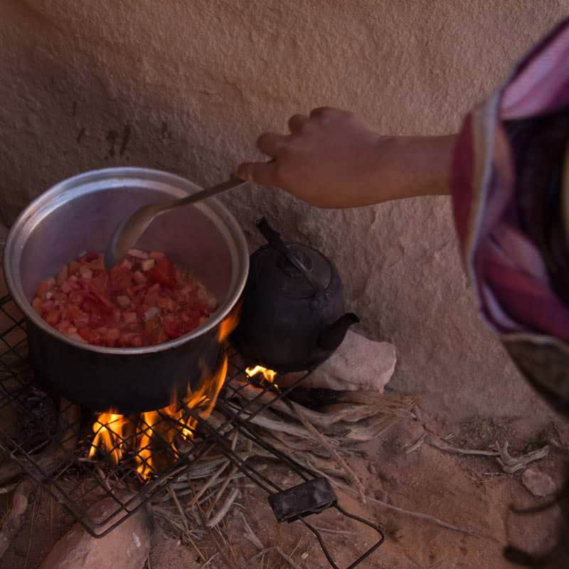 Preparing traditional Bedouin dish Galayet over the wood fire