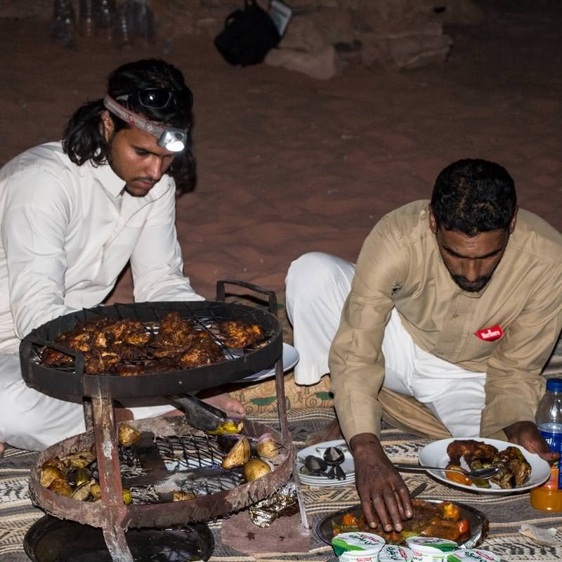 Fawaz and Ali serving food from the Bedouin barbecue, zarb