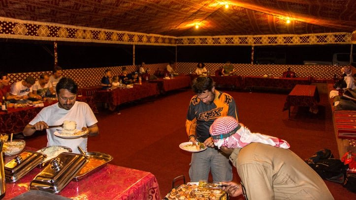 guests enjoying dinner in the communal tent of Wadi Rum Base Camp