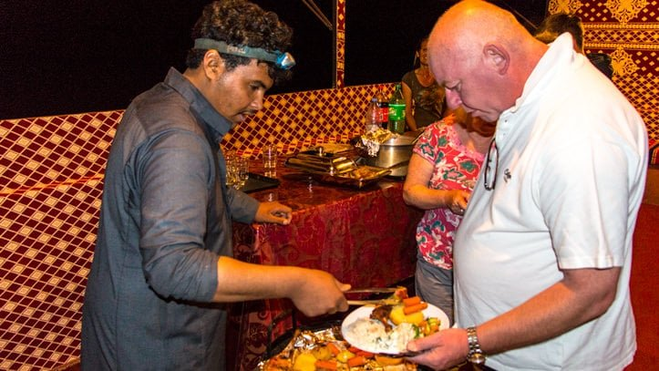 Nawaf serving dinner in the communal tent of Wadi Rum Base Camp