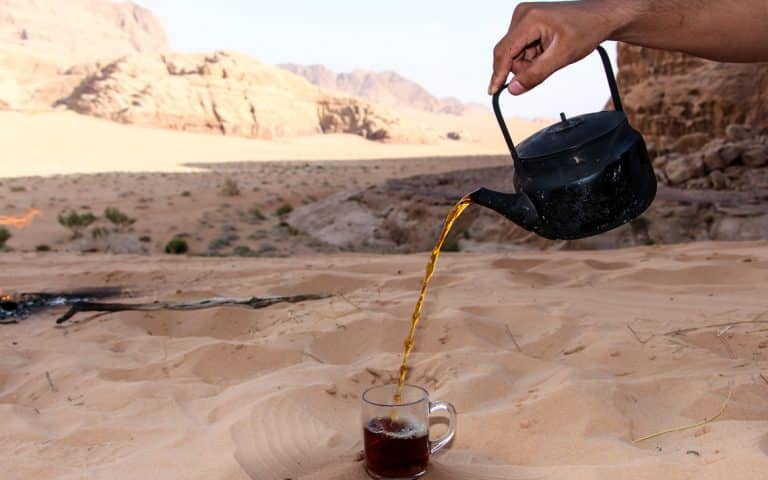 pouring a glass of bedouin tea in wadi rum desert