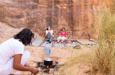 fawaz cooking lunch in front of the relaxing guests in wadi rum