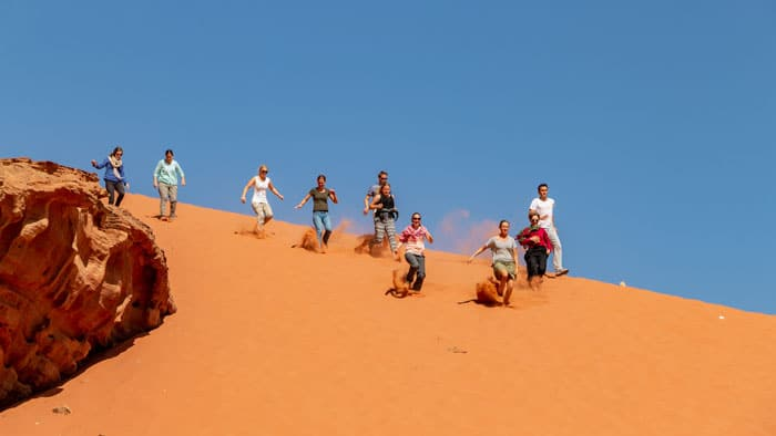 guests running down a sand dune in wadi rum