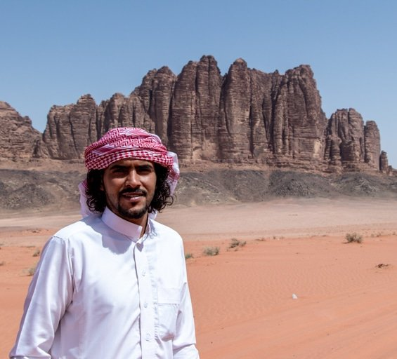 wadi rum nomads - owner fawaz mohammad standing in front of jabal qattar